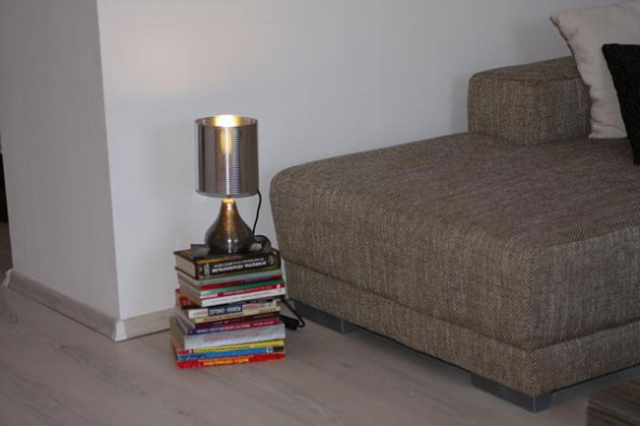 pile of books in the corner of the room as a base lamp