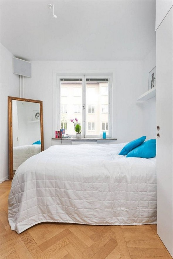 the bedroom is a lovely combination of white and turquoise and manages to contribute to the fresh feel of this apartment