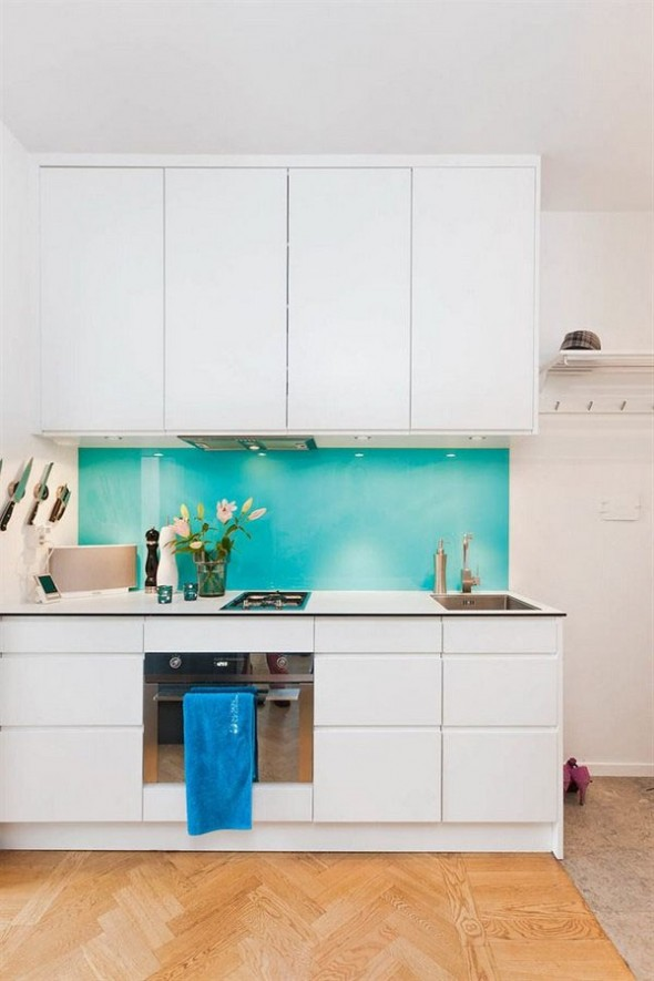 the colored panel in the kitchen gives this cooking corner a friendly and inviting feel